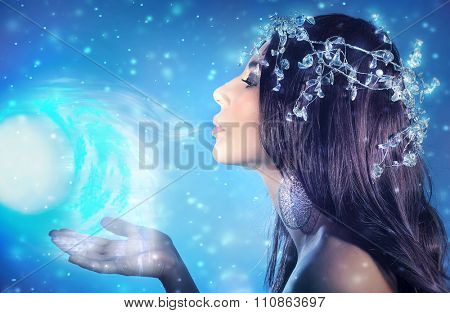 Side view portrait of beautiful snow queen wearing gorgeous diamonds wreath blowing cold winter wind with bright blue light, Christmastime fairy tale