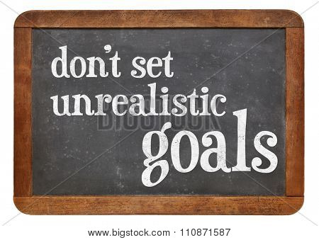 Do not set unrealistic goals - advice or reminder in white chalk on a vintage slate blackboard