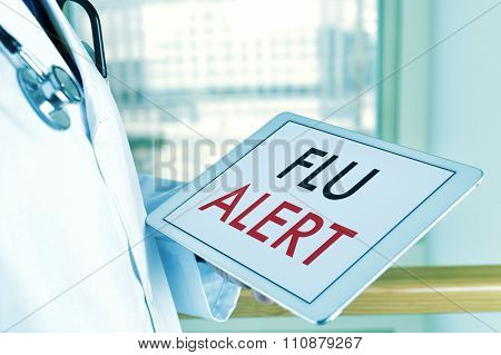 closeup of a young caucasian doctor man with a tablet computer with the text flu alert in its screen