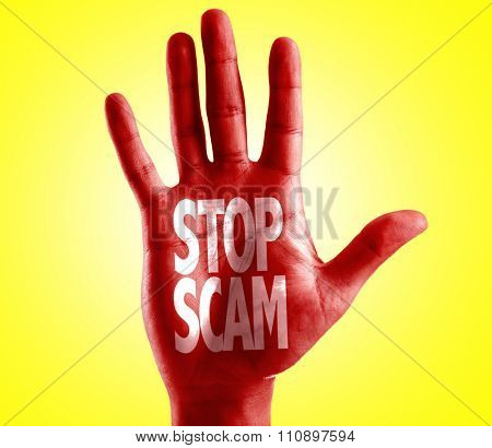 Stop Scam written on hand with yellow background