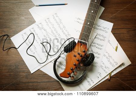 Electric guitar and headphones with music notes on wooden background