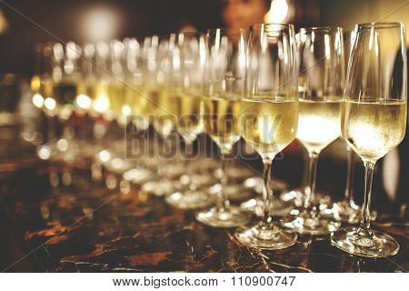 A lot of wine glasses with a cool delicious champagne