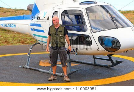 EPERON, REUNION ISLAND, FRANCE - NOVEMBER 7, 2015: Bush pilot against The Eurocopter B3 single turbine on a Helilagon heliport. Helicopter for 6 passengers, max. weight: 2540 kg, max. speed: 278km/h