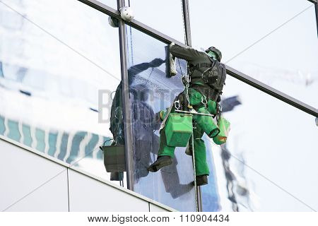 The steeplejack washes windows of a high-rise building
