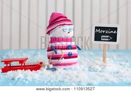 Signpost of the famous ski resort Morzine, France and Snowman with red sled stand near direction sig