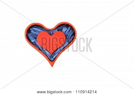 Red painted wooden heart enclosed with blue paper raffia strips in red box isolated on white backgro