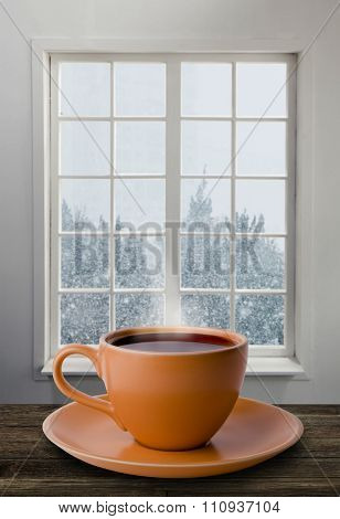 A cup of tea and snowstorm view from the window on the background