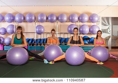 group of woman excersising with fitballs