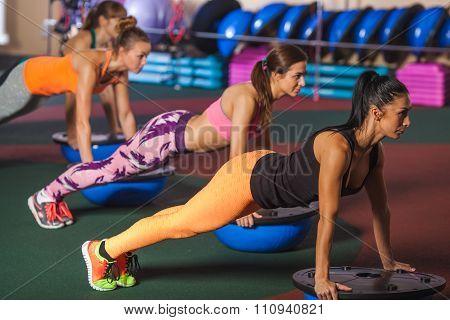 Women balancing on bosu ball