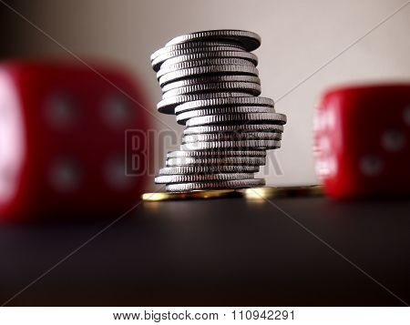 Stack of coins and two red dice