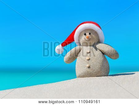 Snowman In Santa Hat At Beach. Christmas Beach Vacation Concept.
