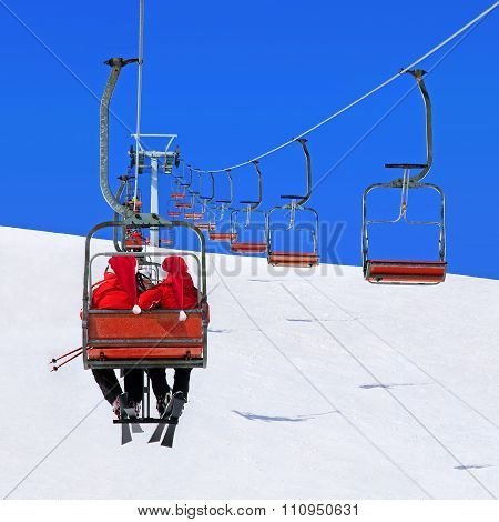Skiers couple in red Santa hats go on a ski lift against winter snowy mountain landscape and blue sky - Christmas greeting card or vacation concept poster