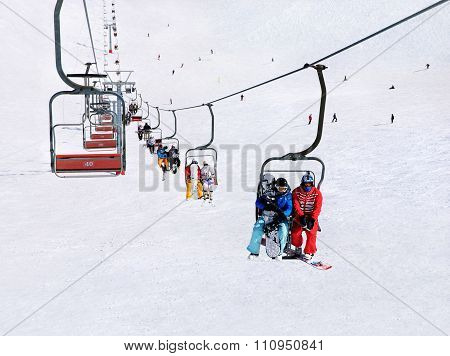 Skiers And Snowboarders On Ski Lift Against Winter Mountain Landscape