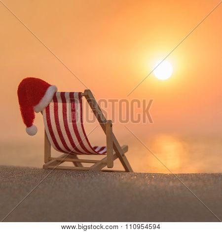Deckchair With Christmas Santa Hat At Ocean Beach During Sunset