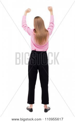 Back view of  business woman.  Raised his fist up in victory sign.    Raised his fist up in victory sign.  Isolated over white background. The girl office worker in black pants raised his fists up.
