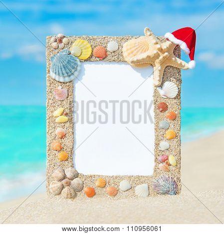Seashells Frame With Christmas Santa Hat Against Ocean Tropical Beach