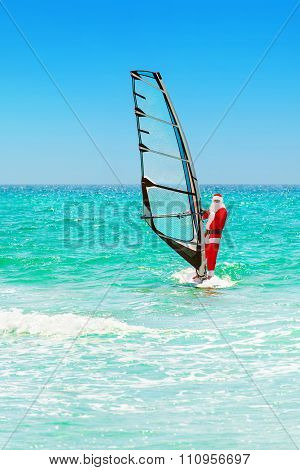 Santa Claus Windsurfer Go Surfing With Sailboard At Ocean Waves