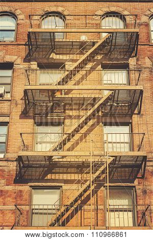 Retro Style Photo Of Building With Fire Escape Ladders, Nyc.