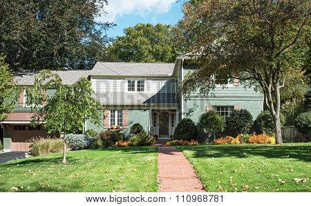 Teal and Mauve House with brick Path & Fall Flowers