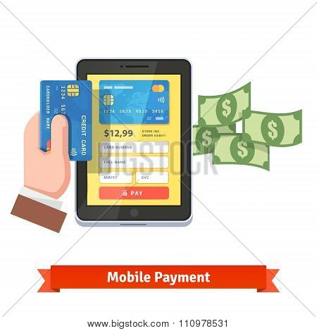 Human hand holding credit card over tablet