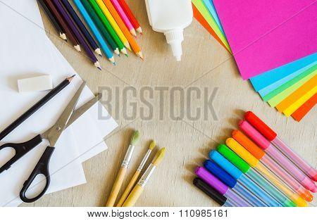 Colored Paper, Felt-tip Pens, Pencils, Brushes On Wooden Background