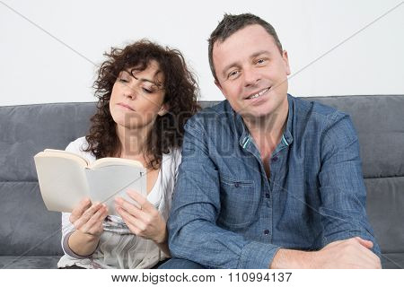 Happy Couple Relaxed Reading A Book At Home On Sofa