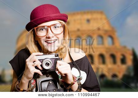 Pretty girl in glasses with retro camera on Colosseum background.