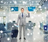 business trip, traveling, luggage and people concept - happy businessman in suit with travel bag and air ticket waving hand over airport background and snow effect poster
