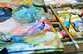 Artistic Brush lies on the palette with colorful paints poster