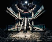 Dramatic view of damaged escalators in abandoned building. Full moon shining on cloudy night sky through collapsed roof. Apocalyptic and evil concept poster