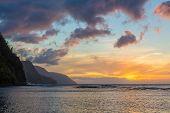 Sun setting over the receding headlands of the Na Pali coast from Ke'e Beach on north of Kauai Hawaii poster
