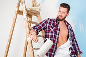 Low angle portrait of handsome pensive painter with open shirt paint roller and vintage ladder posing and looking aside poster