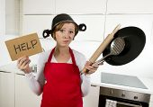 young attractive home cook woman in red apron at kitchen holding pan and household with pot on her head in stress frustrated face expression in rookie amateur and inexperienced cooking concept poster