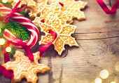 Christmas Holiday Background with Gingerbread cookies, Candy Cane and evergreens border over wooden table. Christmas and New year food. Christmas decoration and sweets on wood background poster