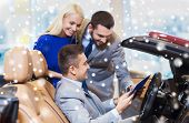 auto business, car sale, consumerism and people concept - happy couple and dealer in cabrio at auto show or salon over snow effect poster
