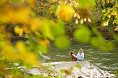 a young girl and her best friend sit by the river and relax. **Note slight blurriness, best at small size. poster