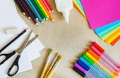 Colored paper felt-tip pens pencils painting brushes scissors glue on wooden background poster