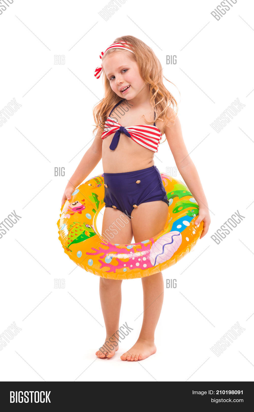 8f5e1fea6e91a Isolated on white beautiful little caucasian blonde girl in red striped  bikini blue bottoms and pink flower wreath hold rubber ring on the waist  look at ...