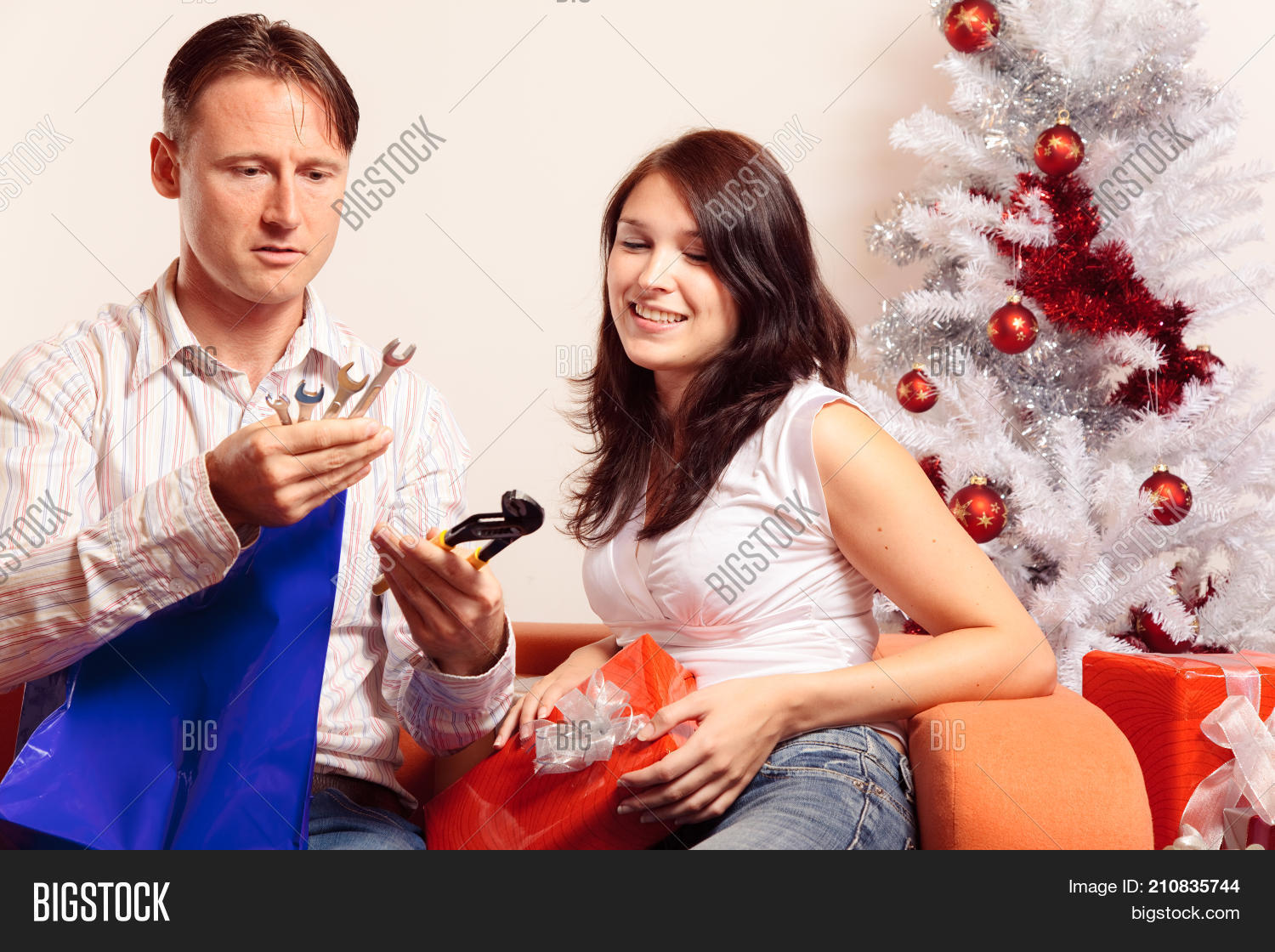 a young couple is sitting on the couch and exchanging christmas gifts he doesn