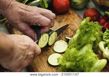 Closeup of hand with knife cutting zucchini