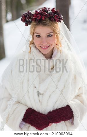 Beautiful bride with bouquet outdoors on winter day.