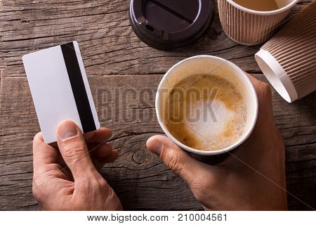 Man holds coffee in one hand and in another credit card. Many cups of coffee are harmful