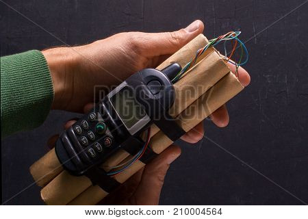 Bomba with explosives and detonator phone in the hands of a terrorist. The denamite sticks are connected by wires with a phonemon. Black background