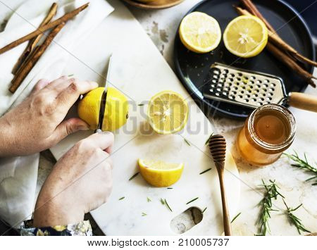 Aerial view of hands with knife cutting lemon