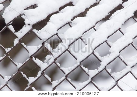 Close-up of barbwire covered by snow . In the park in nature