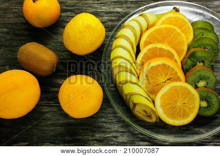 Fresh fruits banana kiwi orange on wooden background. Healthy food. A mix of fresh fruit. Group of citrus fruits. Vegetarian raw fruit. Nutrition for a healthy lifestyle.