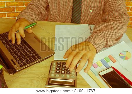 business accounting concept businesswoman and laptop with calculator on table working area. Man doing his accounting financial adviser working - Retro color