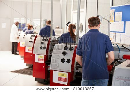 Foreman inspecting trainee engineers working in a factory