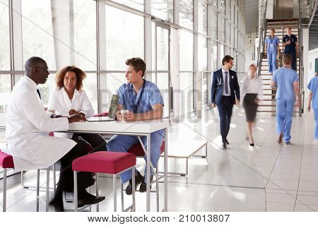 Three healthcare workers talking in a busy modern lobby