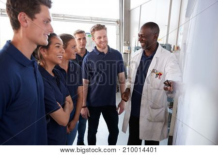 Smiling engineering apprentices gather round whiteboard at a training presentation, close up